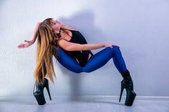 M?oda pi?kna elastyczna dziewczyna w czarnych szpilkach i kombinezonie pozuje w tana studiu Rama w g?r? paska, Jazzowy Wysoki i b obraz stock