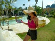 M?oda pi?kna i szcz??liwa Azjatycka Indonezyjska nastolatek kobieta w bikini przy tropikalnym kurortu basenu networking relaksuj? obraz stock