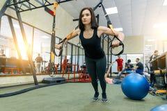 M?oda pi?kna sporty kobieta ?wiczy na sprawno?ci fizycznej troczy system w gym Sprawno?? fizyczna, sport, szkolenie i zdrowy styl obraz stock