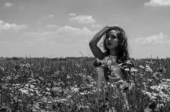 Młoda powabna brunetki dziewczyna w polu z kwiatami maczki i stokrotki na jaskrawym pogodnym letnim dniu Zdjęcie Royalty Free