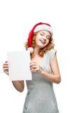 Młoda przypadkowa dziewczyna w Santa kapeluszowym mienia znaku Fotografia Royalty Free