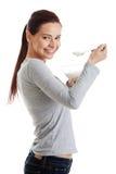 Młoda przypadkowa kobieta je jogurt. Zdjęcia Stock