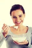 Młoda przypadkowa kobieta je jogurt Fotografia Royalty Free