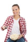 Młoda przypadkowa kobieta z pilot do tv i pucharem popkorn. Zdjęcie Stock