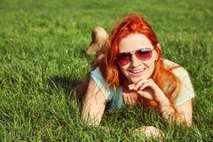 M?oda relaksuj?ca rudzielec dziewczyna k?ama na trawie w okularach przeciws?onecznych kobieta relaks plenerowy zdjęcia royalty free
