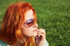 M?oda relaksuj?ca rudzielec dziewczyna k?ama na trawie w okularach przeciws?onecznych kobieta relaks plenerowy obraz royalty free