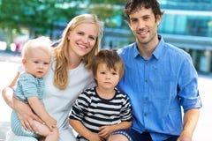 Młoda rodzina z dwa dzieciakami Zdjęcia Stock