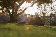 Młoda rodzina z trzy dzieciakami siedzi pod jesieni drzewem Zdjęcie Stock