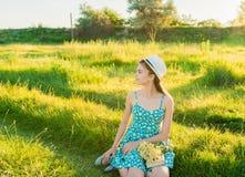 M?oda romantyczna dziewczyna czyta ksi??kowego obsiadanie na trawie obraz royalty free