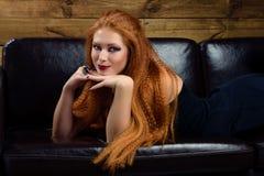 Młoda rudzielec kobieta pozuje na kanapie Zdjęcie Royalty Free