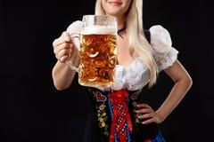 Młoda seksowna kobieta jest ubranym dirndl z piwnym kubkiem na czarnym tle Obraz Royalty Free