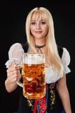 Młoda seksowna kobieta jest ubranym dirndl z piwnym kubkiem na czarnym tle Obraz Stock