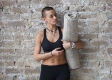 M?oda skinhead kobieta stoi blisko ?ciany z joga mat? zdjęcia stock