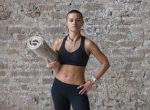 M?oda skinhead kobieta stoi blisko ?ciany z joga mat? fotografia stock