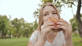 Młoda studencka dziewczyna je hamburger outdoors w parku Przerwa podczas nauki zbiory wideo