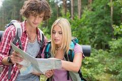 Młoda wycieczkuje pary czytania mapa w lesie wpólnie Zdjęcie Stock