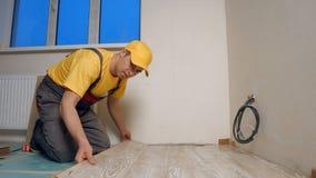 M?oda z?ota r?czka instaluje drewnianej pod?oga w nowym domu obraz royalty free
