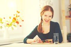 Młoda zdrowa kobieta je warzywa w kuchni w domu Zdjęcia Royalty Free