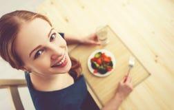 Młoda zdrowa kobieta je warzywa w kuchni w domu Obrazy Stock