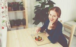 Młoda zdrowa kobieta je warzywa w kuchni w domu Obrazy Royalty Free