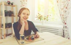 Młoda zdrowa kobieta je warzywa w kuchni w domu Obraz Stock