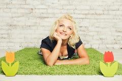 Młode blondynki kobiety w smokingowym lying on the beach na trawie Zdjęcia Royalty Free