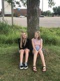 Młode dziewczyny siedzi drzewem zdjęcia royalty free