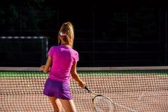 M?odego ?e?skiego gracza w tenisa ?wiczy tenis ?wiczy podczas trenowa? plenerowy na s?dzie przy zmierzchem Widok od plecy fotografia royalty free
