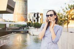 Młodego smiley Kaukaska biznesowa kobieta opowiada na telefonie blisko drapaczy chmur Zdjęcia Stock