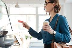 Młodej damy pozycja w cukiernianego mienia kredytowej karcie i kawie Obrazy Royalty Free
