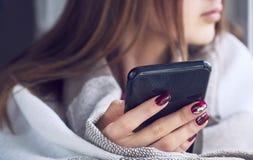 M?odej dziewczyny obsiadanie na nadokiennym parapecie z czarnym smartphone w r?kach zawija? w ciep?ej we?ny koc obrazy stock
