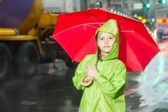 Młodej dziewczyny pozycja w deszczu z deszczowem i parasolem Zdjęcia Royalty Free