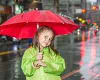 Młodej dziewczyny pozycja w deszczu z deszczowem i parasolem Obraz Stock