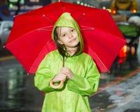 Młodej dziewczyny pozycja w deszczu z deszczowem i parasolem Obrazy Stock