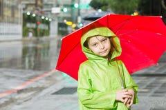 Młodej dziewczyny pozycja w deszczu z deszczowem i parasolem Zdjęcia Stock