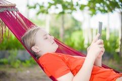 Młodej kobiety czytanie na elektronicznym pastylka czytelniku relaksuje w hamm Obraz Stock