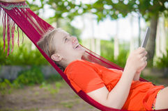 Młodej kobiety czytanie na elektronicznym pastylka czytelniku relaksuje w hamm Zdjęcia Royalty Free