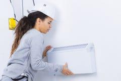 Młodej kobiety dopasowania powietrza conditioner w domu Fotografia Royalty Free
