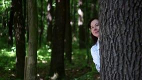 Młodej kobiety falowanie od behind drzewa w lesie zbiory