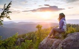 Młodej kobiety obsiadanie na skale, patrzeje Fotografia Royalty Free