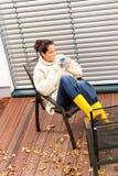 Młodej kobiety obsiadanie pije herbacianego spadku patio Obraz Royalty Free