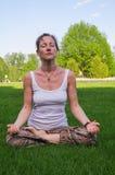 Młodej kobiety obsiadanie w joga pozy medytaci outdoors Fotografia Stock
