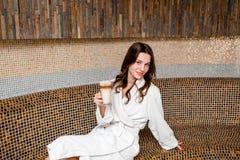 Młodej kobiety obsiadanie w sauna i napoju kawie Zdjęcia Royalty Free