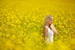 Młodej kobiety odprowadzenie przez pola kwiaty Obraz Stock
