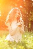Młodej wiosny mody kobiety podmuchowy dandelion w wiosna ogródzie S Zdjęcie Stock