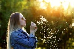 M?odej wiosny mody kobiety podmuchowy dandelion w wiosna ogr?dzie Wiosna Modna dziewczyna przy zmierzchem w wiosna krajobrazu tle zdjęcie stock