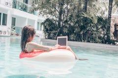 M?ody ?adny kobiety freelancer jest sp?awowy na morzu lub w basenie w p?ywackim okr?gu Dziewczyna jest relaksuj?ca na obrazy stock