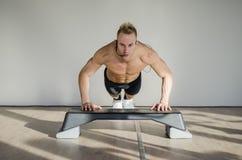 Młody aerobik samiec trener na kroka nauczania klasie Zdjęcie Stock