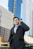 Młody atrakcyjny biznesmen opowiada na telefonie komórkowym outdoors Zdjęcia Royalty Free