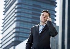 Młody atrakcyjny biznesmen opowiada na telefonie komórkowym outdoors w kostiumu i krawacie Obrazy Stock